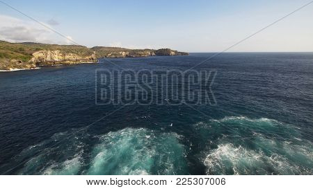 Rocky coast with high cliffs, sea surf with breaking waves on the coast, Nusa Penida, Indonesia. Ocean with waves and rocky cliff. Travel concept.