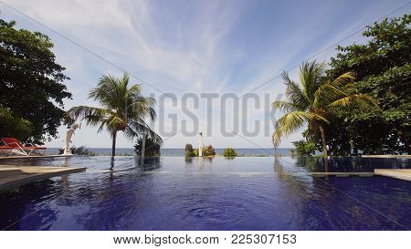 Luxury hotel, resort near at sea with pool among the palm trees. Luxurious open air swimming pool at resort. Swimming pool with turquoise water in hotel. Travel concept.