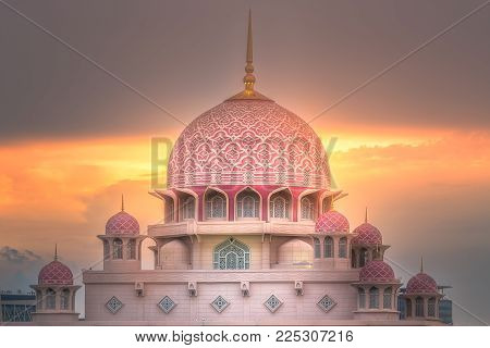 Pink dome of Putra Mosque with sunshine of sunset on dramatic sky Putrajaya, Malaysia