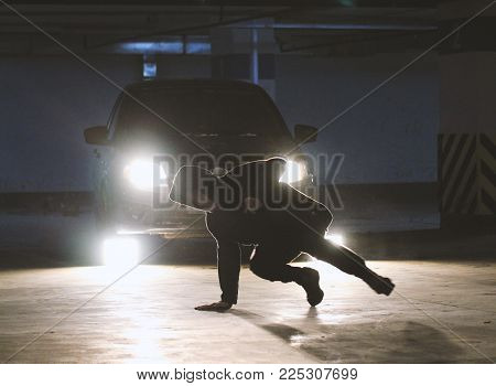 Young man freerunner doing side flips in the garage, parkour acrobatic elements, sports and leisure concept