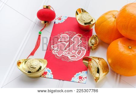 Chinese New year red envelope packet ( ang pow ) with gold ingots and tangerine on white wood table top,Chinese Language on envelop mean Happiness and on ingot mean Wealthy