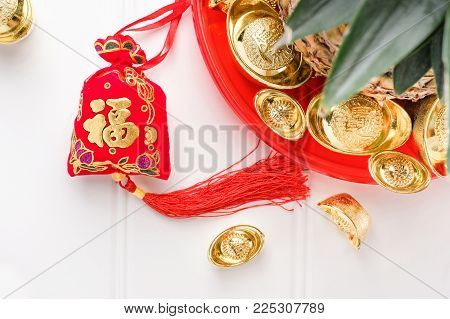Chinese New year red felt bag ( ang pow ) and pineapple with group of gold ingots in red tray on white wood table.on ingots mean wealthy and on bag mean happiness.pineapple in Chinese mean luck