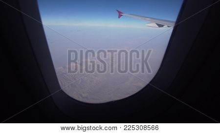Mountain range from the airplane window. Airplane wing. Aerial view on mountains through window of an aircraft. Mountain from the airplane window. Travel concept.