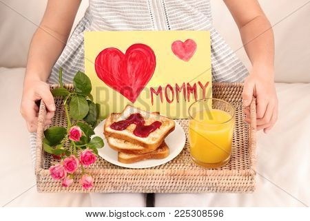 Little girl holding tray with breakfast and greeting card for her mommy on Mother's Day indoors poster