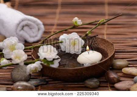 Spa setting with cherry ,stones ,candle ,towel, bowl on mat