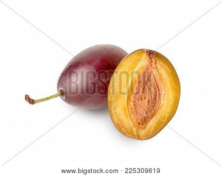 Plum closeup with a green tail and half plum with bone, isolated on white background. Freshly berry of plum