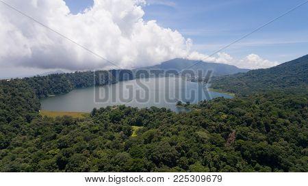 Aerial view of Lake Tamblingan, a caldera lake at Bali. Beautiful lake with turquoise water in the mountains of the island of Bali. Landscape, lake among mountains, sky, clouds.