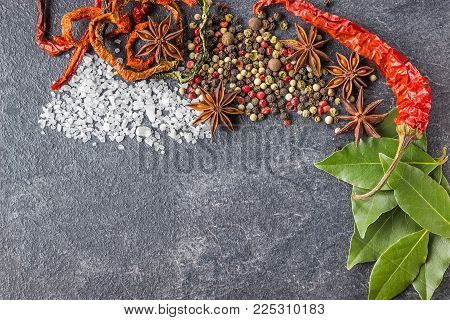 Spices on the stone black background. Condiments on a dark table. Seasoning for cooking. Seasoning mix.