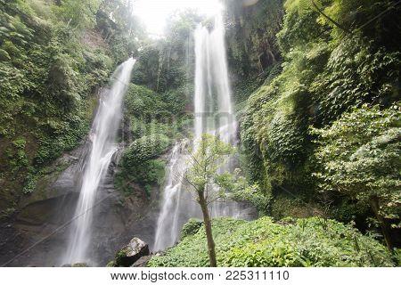 Waterfall in green rainforest. Triple waterfall Sekumpul in the mountain jungle. Bali, Indonesia. Travel concept.