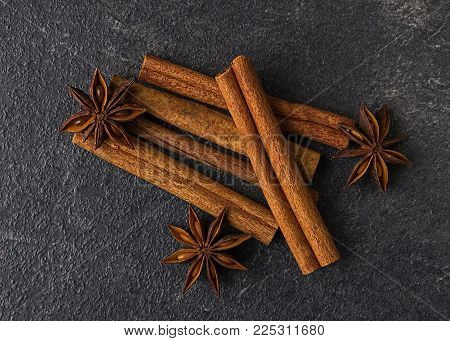 Cinnamon sticks and anise stars on a black stone background. Condiments on a dark table.