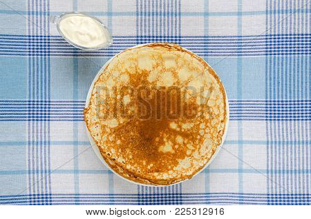 Russian pancakes with sour cream on checker tablecloth. Overhead food shots.
