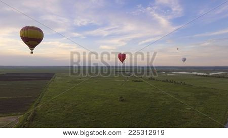 Aerial view Hot air balloons in the sky over a field in the countryside in the beautiful sky and sunset. Aerostat fly in the countryside.