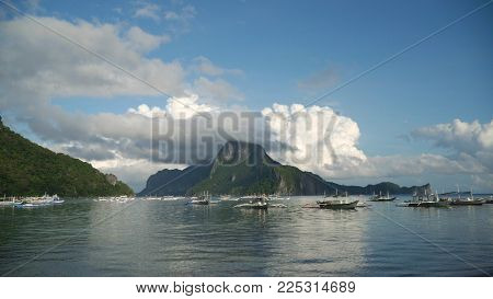 Mountain island, rocks, sea, clouds. Sailing boats and yachts in the bay, tropical lagoon. Seascape with island, mountains, boats on the water. Tropical landscape. Tropical island. Philippines, El Nido. Travel concept