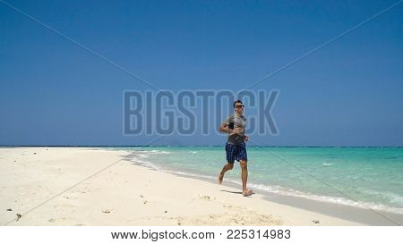 Man running along beach. Fitness sports runner man jogging on beach. Handsome young fit sporty male athlete running outside on beautiful beach training.