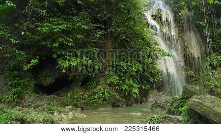 Waterfall in green forest in jungle. Beautiful waterfall in the mountains. Tropical rain forest with waterfall. Philippines, Cebu. Travel concept.