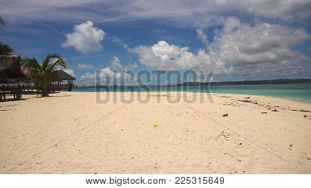 Beach with white sand with beach house on a tropical island Daco. Beautiful sky, sea, resort. Seascape: Ocean and beautiful beach paradise. Philippines. Travel concept.