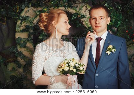 Beautiful bride in a white dress and a young groom in a blue suit indoors in the Studio during a photoshoot