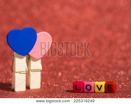 Wooden Heart Clip With Love Text From Bead Colorful On The Red Floor And Background. Copy Space For