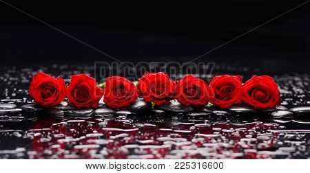 Row of red rose, petals, with white candle and therapy stones
