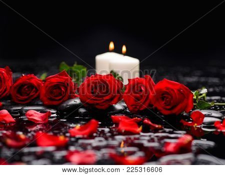 Lying down red rose with white candle and therapy stones