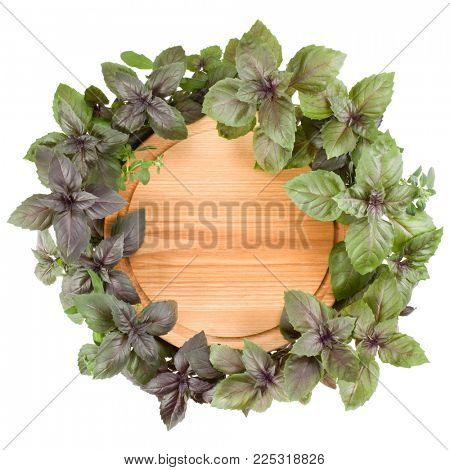 Empty round wooden cutting board. Various sweet basil herb leaves edged.. Healthy food concept. Top view with copy space.
