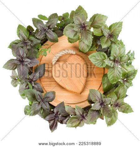 Round cutting board with wooden heart in centre. Various sweet basil herb leaves edged.. Healthy food concept. Top view.