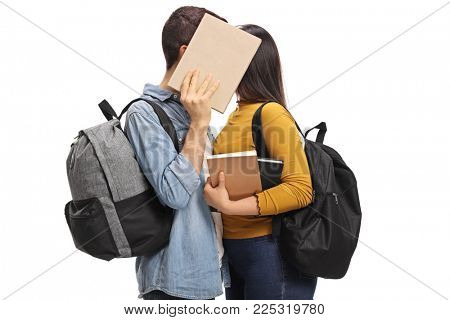 Teen students kissing behind a book isolated on white background