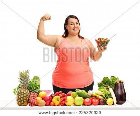 Overweight woman holding a bowl of salad and flexing her biceps behind a table with vegetables and fruit isolated on white background