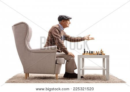 Mature man seated in an armchair playing a game of chess and arguing with someone isolated on white background