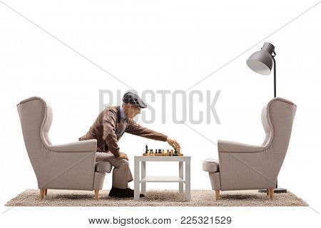 Senior playing a game of chess by himself isolated on white background