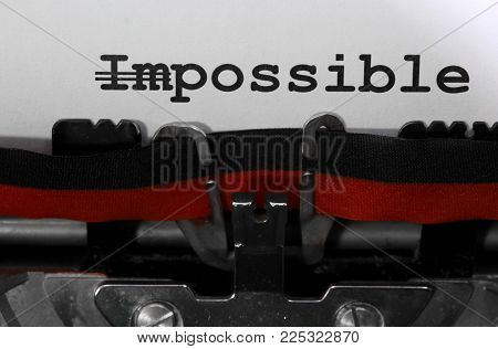 Word IMPOSSIBLE with the text IM deleted and then everything is possible written the old typewriter on white page