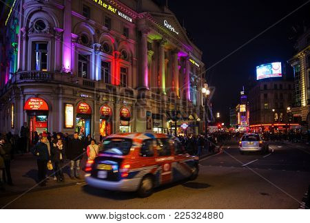 LONDON, UK - OCTOBER 30, 2012: Taxicab moves along illuminated Ripley's Believe It or Not! Museum at Piccadilly Circus road junction, London's West End, City of Westminster.
