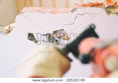 Construction worker using pneumatic hammer, construction site concept.