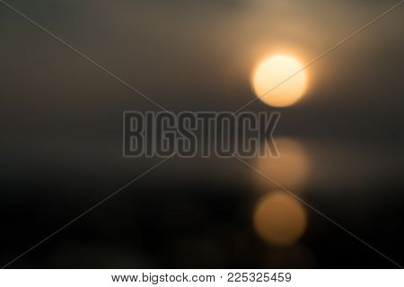 Background image defocused abstract rising sun above horizon refelected below Sunrise at Koh Samui along coral coastline.