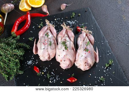 Fresh  raw meat quails ready for cooking on the  slate board