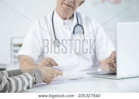 Close-up Of Elder Doctor Giving Medical Suggestions To His Patient In An Office