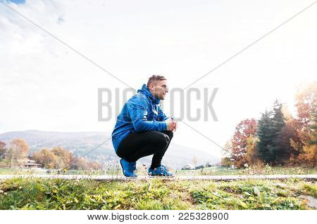 Young runner in blue jacket outside in colorful sunny autumn nature resting on an asphalt path. Trail runner training for cross country running.