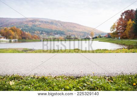 An asphalt path in front of a lake in the autumn nature. Rural scene.