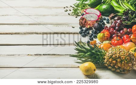 Helathy raw vegan food cooking background. Fresh fruit, vegetables, greens, superfoods over white wooden table, copy space. Clean eating, alkaline diet, vegetarian concept