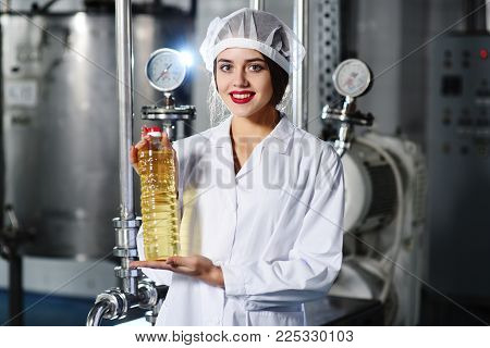 a beautiful young girl in white uniform or a working dressing gown with a bottle of sunflower oil in her hands on the background of the food production line of refined oil.