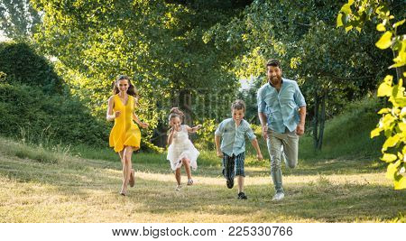 Active young parents with a healthy lifestyle running together with their two competitive children outdoors in a summer day