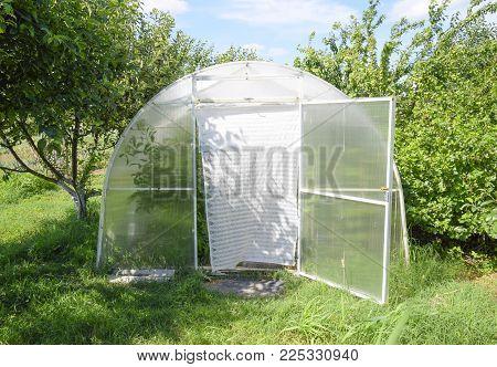 Greenhouse polycarbonate in a private garden. Farmland.