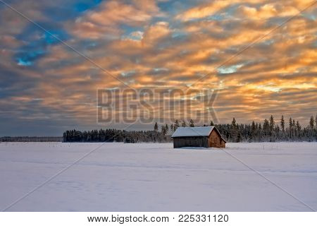 The Sun Sets Behind The Dramatic Clouds Over A Frosty Field With An Old Barn House In The Northern F