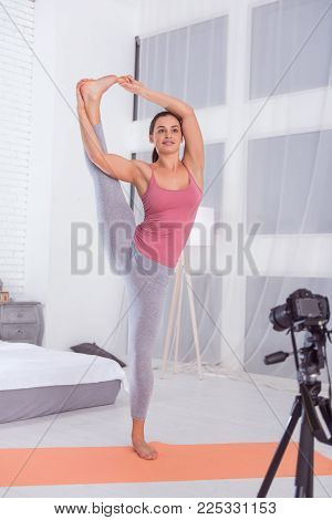 Feeling vigorous. Beautiful exuberant muscular dark-haired young woman smiling and doing exercises on the carpet while making a video for her blog