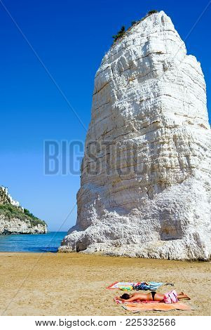Vieste, Italy - September 5, 2006:  A lady sunbathes on the beach with the Pizzomunno monolith in the background