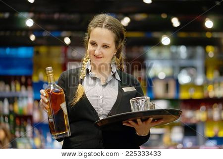 A barmaid girl carries a bottle of whiskey with glasses on a tray to the client of the hotel bar. The concept of service.