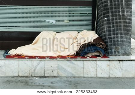 Poor homeless person covered with a blanket sleep in the shadow on the street