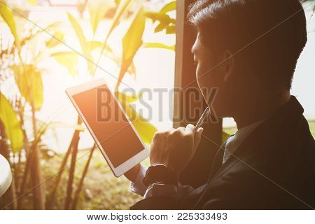 Confident Businessman In Suit Holding Touchpad While Sitting At Cafe. Young Asian Startup Man Using