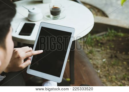 Businessman In Suit Holding Touchpad While Sitting At Cafe. Young Asian Startup Man Using Digital Ta