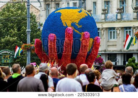Debrecen, Hungary - August 20, 2017: Spectators view a flower composition during the 48th Flower Carnival in the center of Debrecen, Hungary.